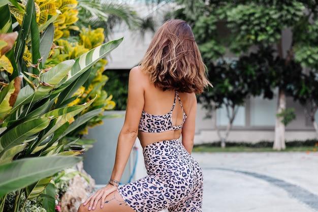 Mode stilvolle junge kaukasische passform sportliche frau in leopard cami top und biker shorts außerhalb hält protein-shaker
