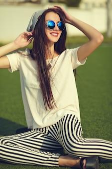 Mode stilvolle schöne junge brünette frau modell im sommer hipster freizeitkleidung posiert auf straßenhintergrund im park