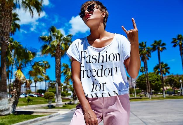 Mode stilvolle schöne junge brünette frau modell im sommer hipster helle bunte freizeitkleidung posiert zeigt rock'n'roll zeichen