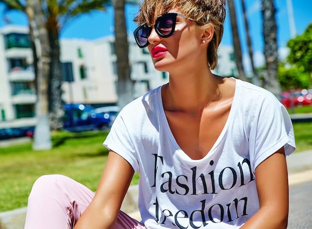 Mode stilvolle schöne junge brünette frau modell in sommer hipster freizeitkleidung posieren und sitzen auf asphalt