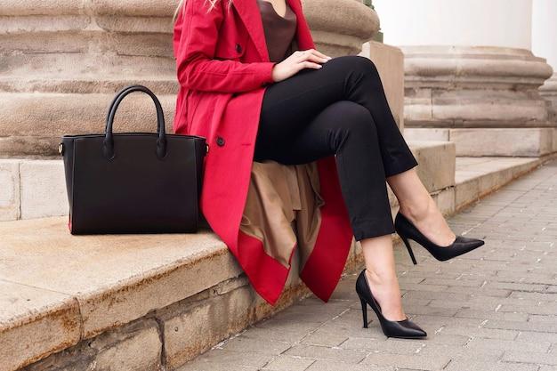 Mode straßenporträt frau tragen trendigen roten trenchcoat, fersen, große tasche halten, auf treppen sitzen.