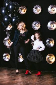 Mode süßes kleines mädchen und schöne frau mit einem bündel von schwarzen luftballons gegen die wand mit lampen