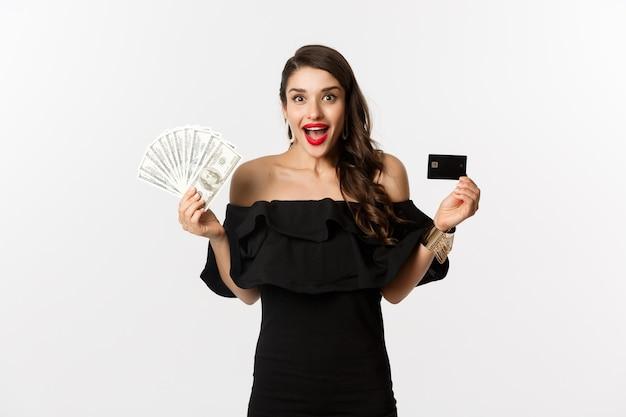 Mode- und einkaufskonzept. aufgeregte frau im schwarzen kleid, kreditkarte und dollar zeigend, lächelnd und starrend in die kamera, weißer hintergrund.