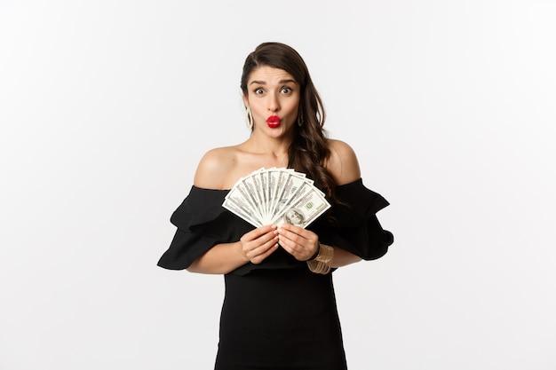 Mode- und einkaufskonzept. aufgeregte frau im schwarzen kleid, mit den roten lippen, zeigt gelddollar und schaut erstaunt auf kamera, weißer hintergrund.