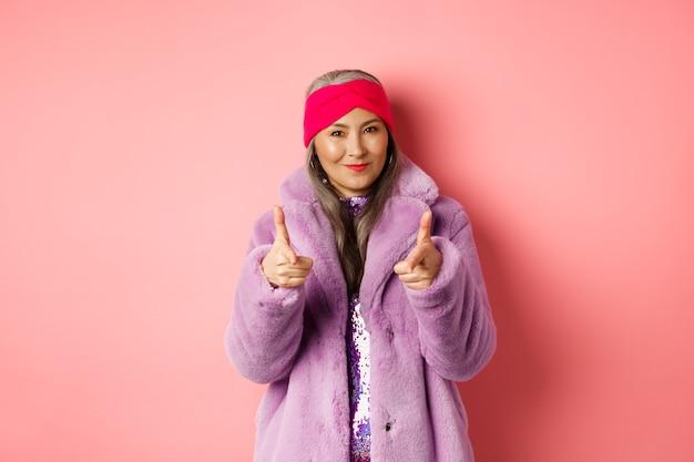 Mode- und einkaufskonzept. coole asiatische seniorin in stilvollem kunstpelzmantel, die mit den fingern auf die kamera zeigt und sie auffordert, das promo-angebot zu überprüfen, das über rosafarbenem hintergrund steht.