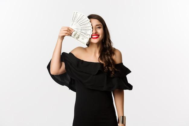 Mode- und einkaufskonzept. glückliche junge frau im schwarzen kleid, mit roten lippen, geld haltend und zufrieden lächelnd, über weißem hintergrund stehend.