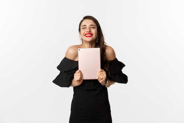 Mode- und einkaufskonzept. glückliche junge frau mit roten lippen, tragendes schwarzes kleid, freudig und haltend digitales tablett, gewinnenden preis, weißer hintergrund.