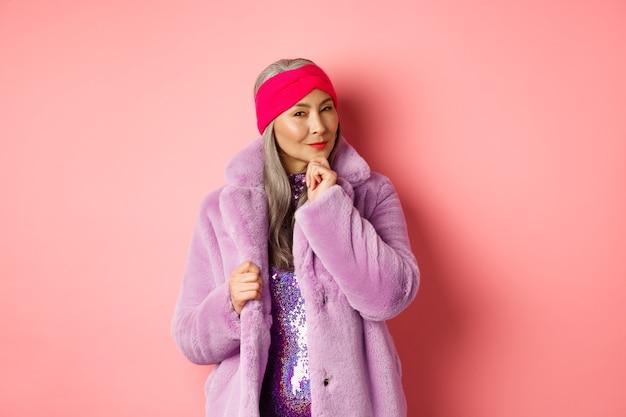 Mode- und einkaufskonzept. stilvolle alte asiatische dame in lila kunstpelzmantel, die fasziniert aussieht, sich für werbung interessiert, lächelt und denkt, rosa hintergrund.