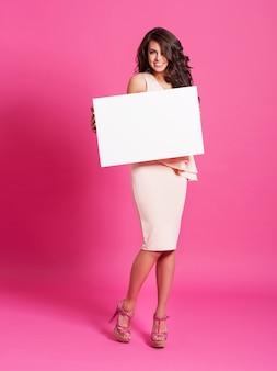 Mode und elegante frau, die whiteboard hält