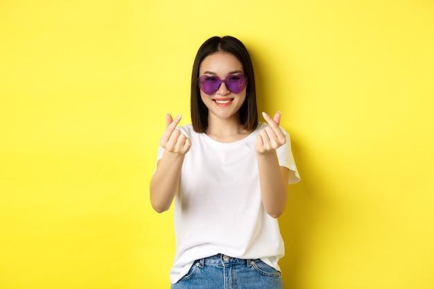 Mode- und lifestyle-konzept. attraktive asiatische frau in herzförmiger sonnenbrille, die fingerherzen zeigt und glücklich in die kamera lächelt und über gelbem hintergrund steht.