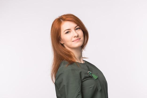 Mode- und menschenkonzept. schöne junge frau mit den roten haaren, die über weiß mit kopienraum lächeln