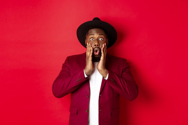 Mode- und partykonzept. beeindruckter schwarzer mann in edlem outfit, der mit völligem unglauben in die kamera starrt, keucht und überrascht aussieht und auf rotem hintergrund steht.