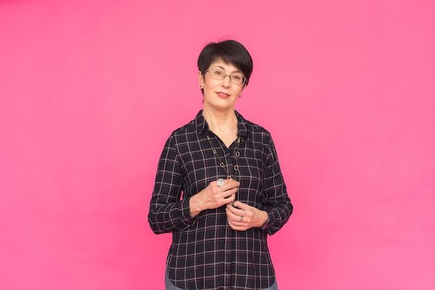 Mode- und personenkonzept - attraktive frau mittleren alters in gläsern über rosa oberfläche