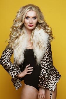 Mode- und personenkonzept: schöne sinnliche frau mit luxuriösem blondem haar in dessous und pelzmantel, die über gelbem hintergrund aufwerfen