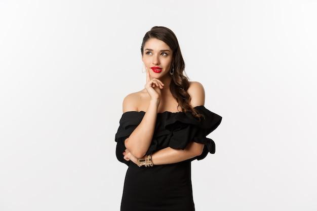 Mode und schönheit. durchdachte junge frau im schwarzen kleid, zufrieden lächelnd und denkend, eine idee habend, weißer hintergrund