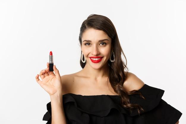Mode- und schönheitskonzept. schöne frau im schwarzen kleid, das roten lippenstift zeigt und lächelt, stehend auf weißem hintergrund. platz kopieren