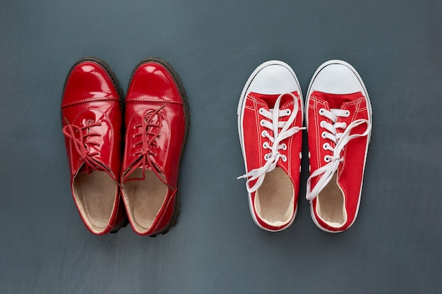Mode und stil. klassische rote lacklederschuhe für damen und trendige rote turnschuhe für jugendliche auf grauem holzhintergrund. draufsicht.