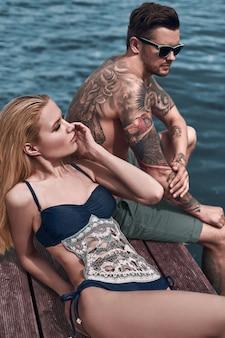 Mode, verführerisches mädchen im gestrickten badeanzug, der eine sonnenbräune erhält