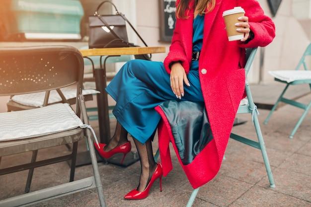 Modeaccessoires der stilvollen frau, die im straßencafé der stadt im roten mantel sitzt, der kaffee trinkt, der blaues seidenkleid, hochhackige schuhe trägt