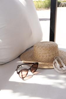 Modeaccessoires für damen. stilvolle weibliche sonnenbrille, strohhut, einkaufstasche auf weißer lounge-couch mit kissen