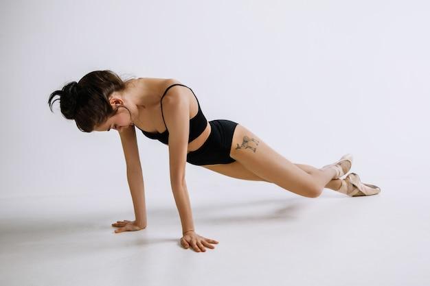 Modeballett. junge balletttänzerin im schwarzen body gegen weißen hintergrund. kaukasische ballerina wie ein model.