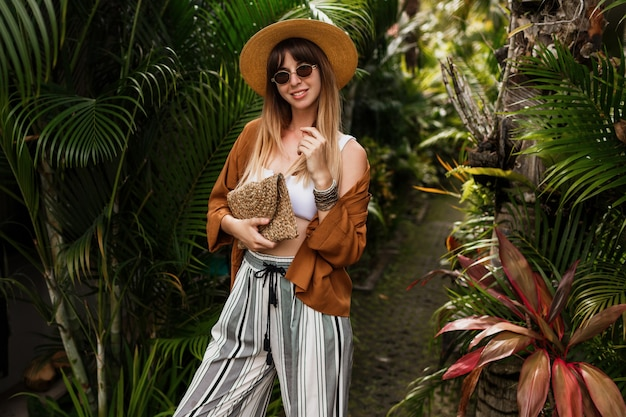 Modebild der sexy anmutigen frau im strohhut, der auf tropischen palmblättern aufwirft