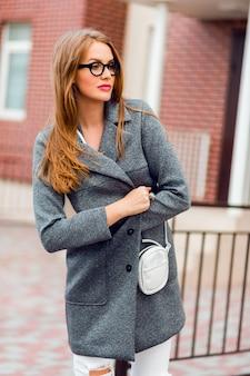 Modebild der stilvollen blonden frau im grauen mantel, der auf der straße geht.