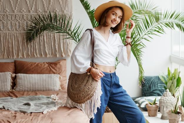 Modebild der stilvollen brünetten frau, die zu hause im boho-stil aufwirft