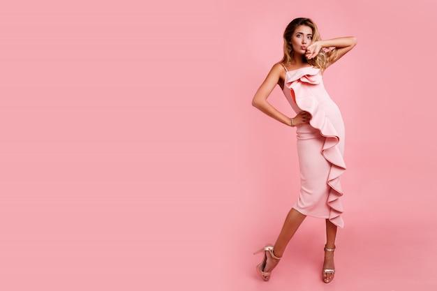 Modebild der vollen höhe der blonden frau mit der perfekten gewellten frisur im rosa partykleid, das aufwirft. high heels. überraschungsgesicht. leerzeichen für text.