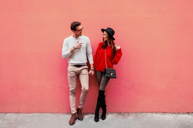 Modebild des eleganten stilvollen paares in der liebe, die hände hält und einander mit vergnügen ansieht. langhaarige frau im roten strickpullover mit ihrem freund posiert.