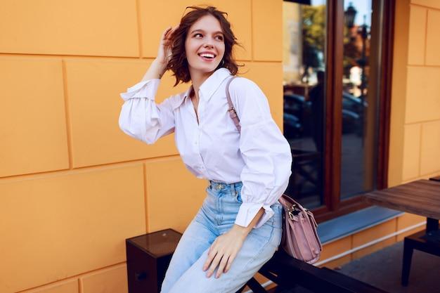Modebild des hübschen brünetten mädchens mit der kurzen frisur in der stilvollen lässigen weißen bluse und in den jeans. schwarze lederstiefel an den absätzen. mädchen, das nahe modernem café mit gelben wänden sitzt.
