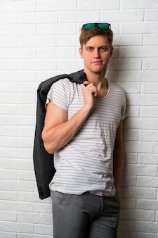 Modebild des hübschen mannes im lässigen outfit, das über weiße backsteinmauer aufwirft.