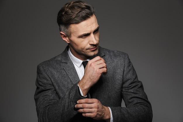 Modebild des maskulinen mannes gekleidet im geschäftsanzug, der beiseite schaut, während manschettenknopf oder knopf auf ärmel der jacke, lokalisiert über graue wand befestigt