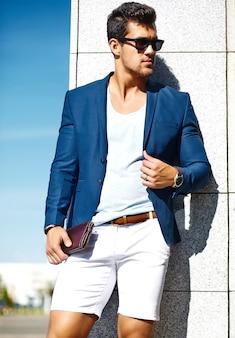 Modeblick junger stilvoller überzeugter glücklicher hübscher geschäftsmannmodellmann in der blauen klage kleidet in der straße in der sonnenbrille hinter himmel