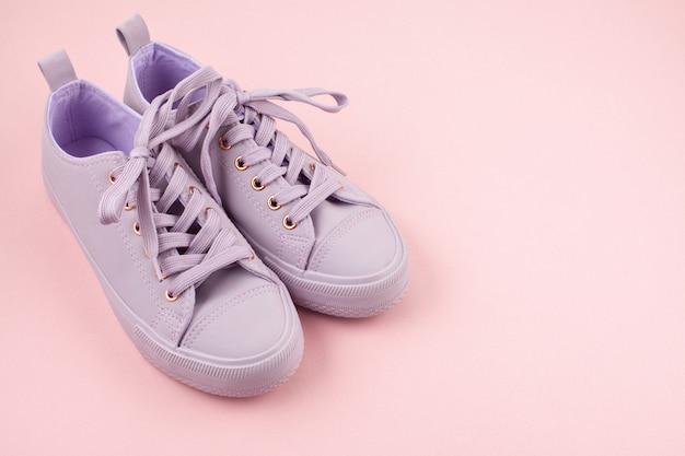Modeblog oder magazinkonzept. rosa weibliche turnschuhe über pastellrosahintergrund. flachgelegt, draufsicht