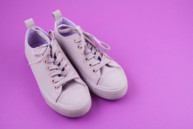 Modeblog oder magazinkonzept. rosa weibliche turnschuhe über pastellrosahintergrund.