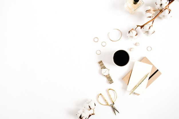 Modeblog schreibtisch im goldstil mit damenaccessoire-kollektion: goldene uhren, schere, kaffeetasse, notizbuch und baumwollzweig auf weiß