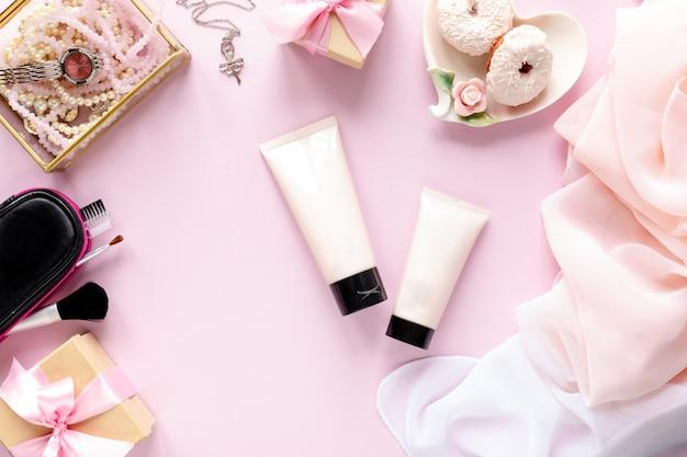Modeblogger-arbeitsbereich mit laptop und weiblichem zubehör, kosmetische produkte auf rosa tisch.
