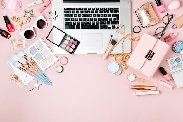 Modeblogger-arbeitsplatz mit laptop und weiblichem accessoire, kosmetikprodukte auf blassrosa tisch. flach liegend, ansicht von oben