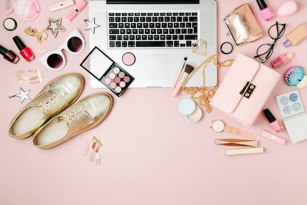 Modeblogger-arbeitsplatz mit laptop und weiblichen accessoires-kosmetikprodukten auf blassrosa tisch