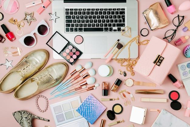 Modeblogger-arbeitsplatz mit laptop und weiblichen accessoires-kosmetikprodukten