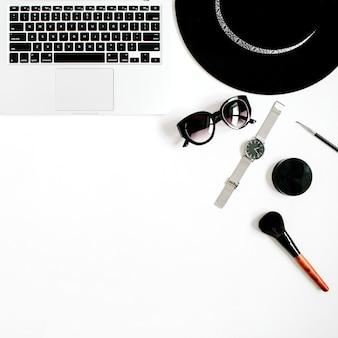 Modeblogger-büroschreibtisch mit laptop und schwarzer angeredeter frauenkleidungs- und -zusatzsammlung auf weißem hintergrund. flache lage, ansicht von oben.