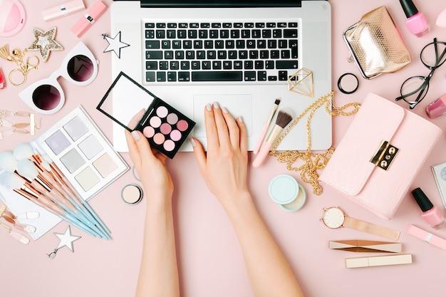Modeblogger, der mit laptop arbeitet. arbeitsbereich mit weiblichem zubehör, kosmetikprodukte auf hellrosa tisch. flach liegend, ansicht von oben
