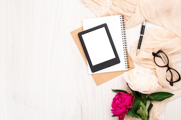 Modeblogger-innenministeriumschreibtisch mit fraueneinzelteilen: moderner ebook leser, papiernotizblock, beige schal, pfingstrosenblumen, gläser