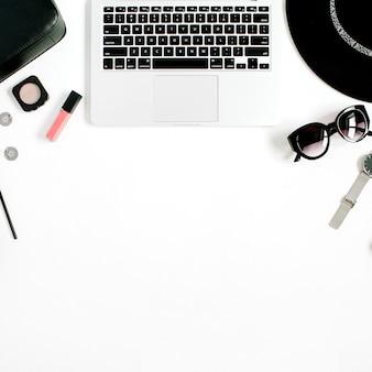 Modeblogger-schreibtisch mit laptop und schwarz gestylter frauenkleider- und -zubehörkollektion auf weiß