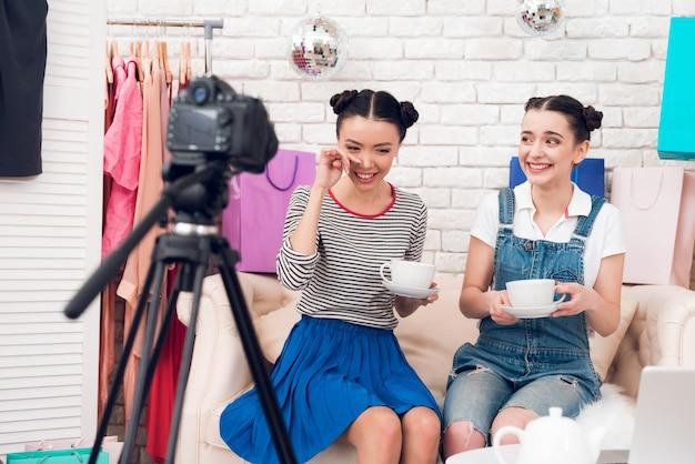 Modebloggermädchen trinken tee zur kamera.