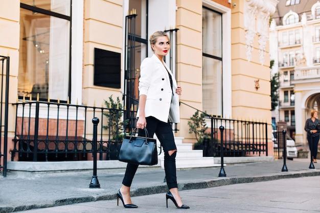 Modeblonde frau auf absätzen in weißer jacke geht auf straße. sie lächelt zur seite.