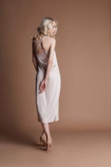 Modeblondine in einer langen schönen kleideraufstellung