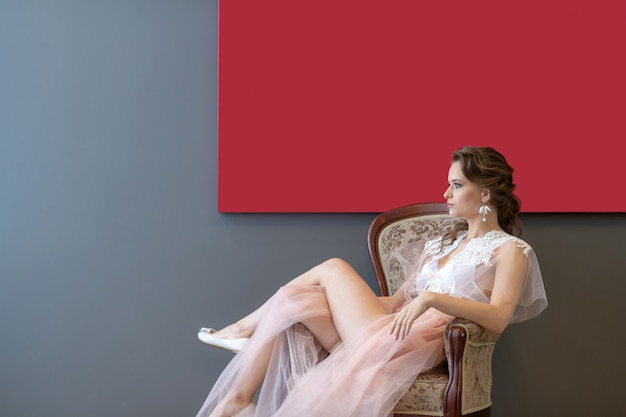 Modebraut, die im stuhl im peignoir unter rotem bild sitzt