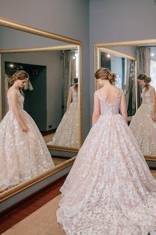 Modebraut im weißen hochzeitskleid, das in der umkleidekabine aufwirft.